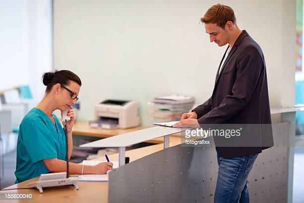 Médecin patient le réceptionniste lors de l'enregistrement