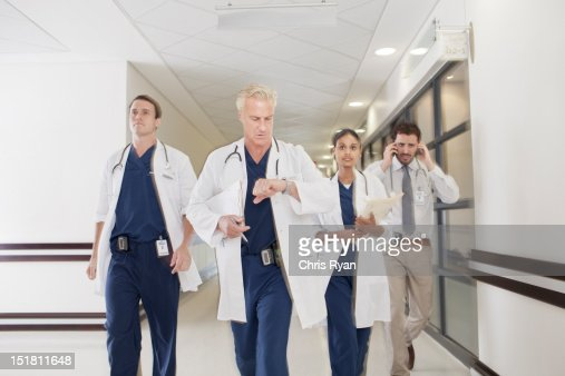 Doctors rushing down hospital corridor : Stock Photo