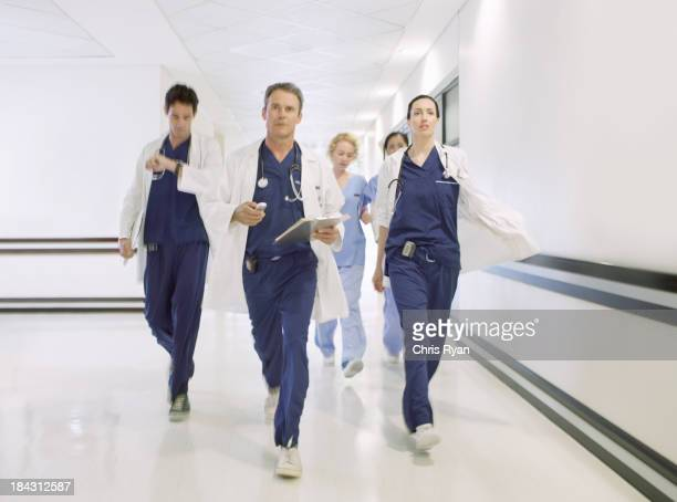 Doctors rushing down hospital corridor