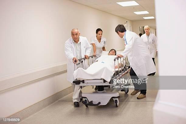 Doctors rushing patient down hallway