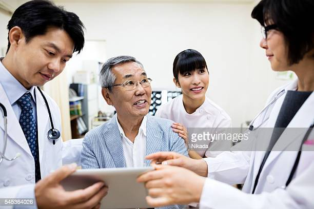 Doctors showing digital tablet to smiling senior man in hospital