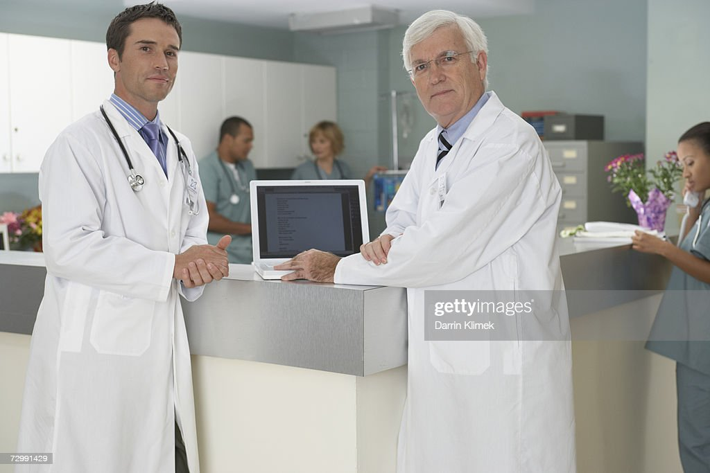 Doctors standing at reception area,  smiling : Stock Photo