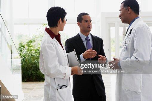Doctors talking to businessman : Bildbanksbilder