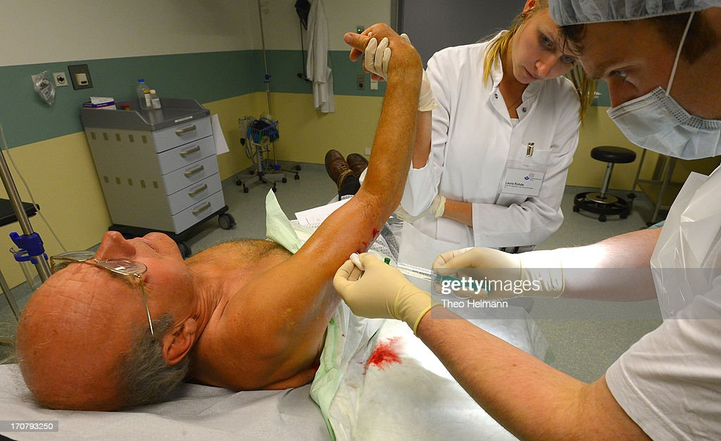 Doctors tend to a man who had been bitten by a dog at the Unfallkrankenhaus Berlin (UKB) hospital in Marzahn district on June 17, 2013 in Berlin, Germany. The UKB hospital has among the most modern emergency care services in Germany.