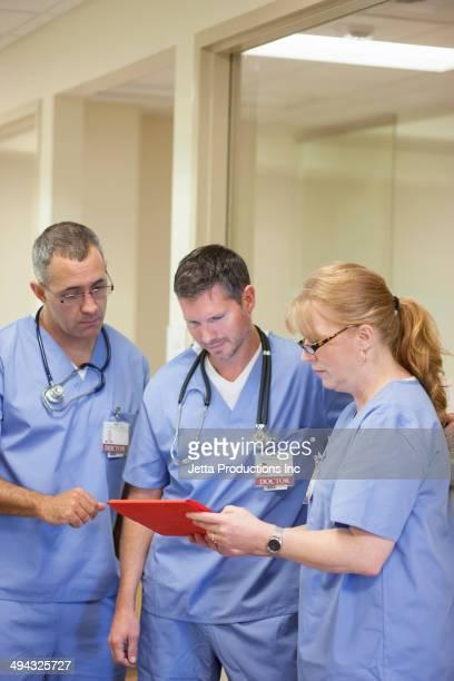 Doctors using digital tablet in hospital