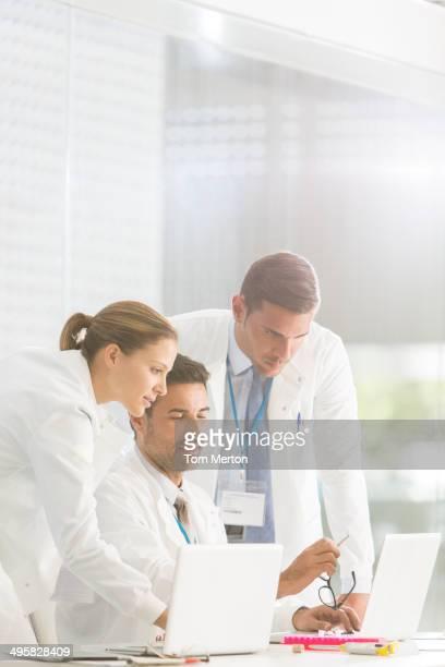 Doctors using laptop in hospital