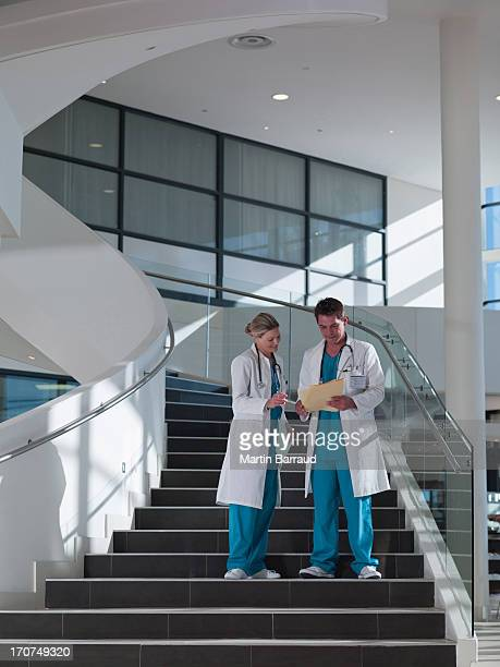Doctors walking down staircase in hospital
