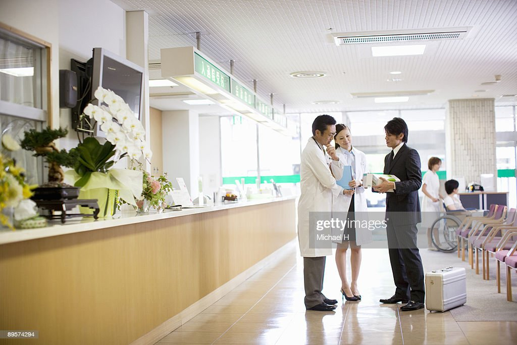 Doctors who speak with salesman of medical supply : Stock Photo