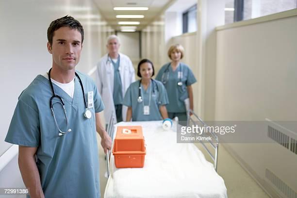 Doctors with hospital trolley walking in corridor