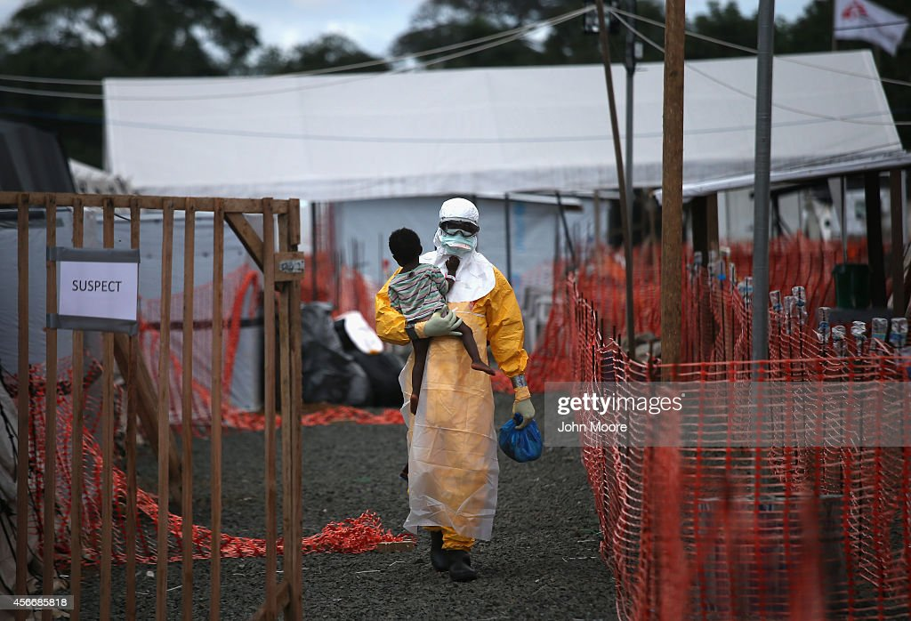 Doctors Without Borders health worker in protective clothing carries a child suspected of having Ebola in the MSF treatment center on October 5 2014...