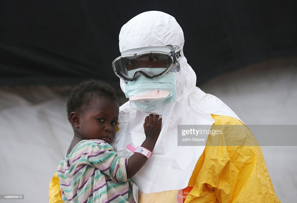 Doctors Without Borders health worker in protective clothing holds a child suspected of having Ebola in the MSF treatment center on October 5 2014 in...