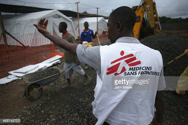Doctors Without Borders staffer supervises as construction workers complete the new MSF Ebola treatment center on August 17 2014 near Monrovia...