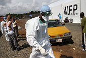 A Doctors Without Borders worker in protective clothing passes by as people arrive requesting to be tested for the Ebola virus at the MSF treatment...