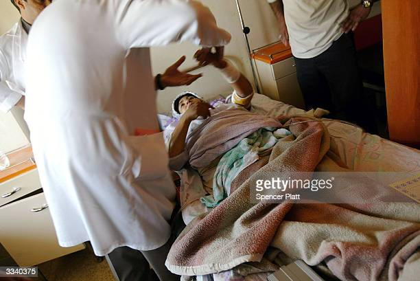 Doctors work on Fadhila Nuseif a wounded pregnant woman from the besieged town of Fallujah April 11 2004 in Baghdad Iraq With hundreds of civilian...