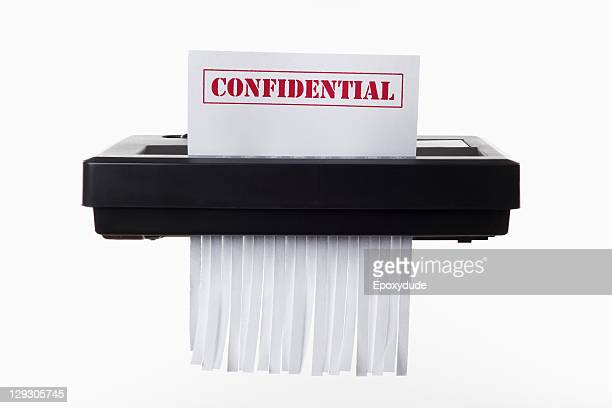 A document with CONFIDENTIAL on it being shredded in a paper shredder