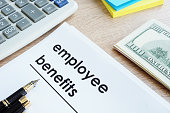 Document with title employee benefits on a desk.