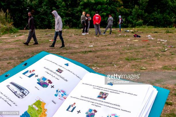 TOPSHOT A document written in Arabic and English explaining the transfer by bus to a reception centre is distributed to migrants as a member of OFII...