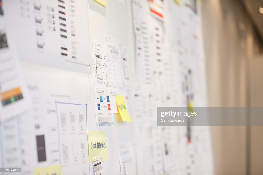 Documents and adhesive notes on wall in office : Stock Photo