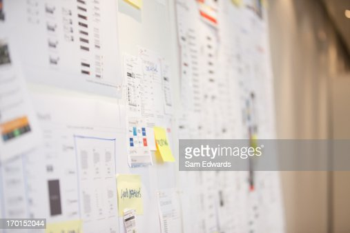 Documents and adhesive notes on wall in office
