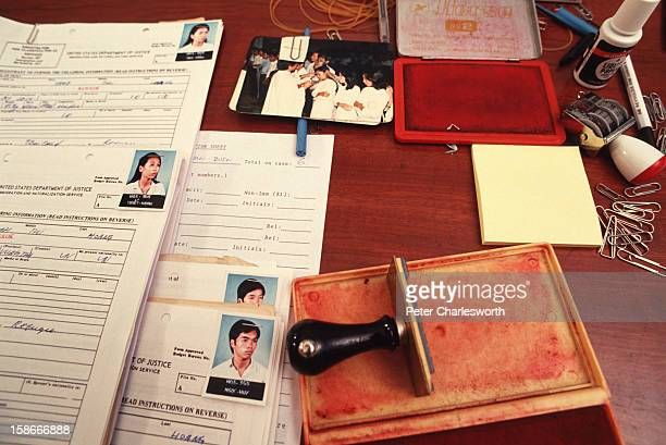 Documents of family members litter the desk of American Immigration and Naturalization Service officials who will determine whether they may leave...