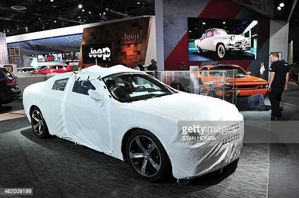 A Dodge car under wraps in Cobo Hall as preparations are made for the North American International Auto Show January 12 2014 in Detroit Michigan The...