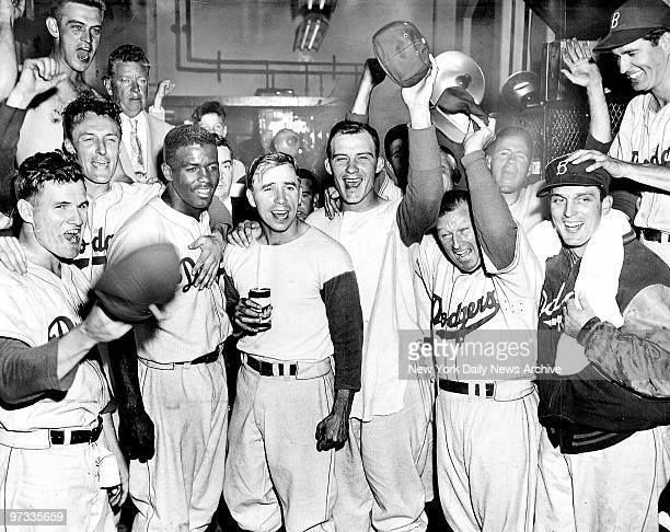 Dodgers celebrate in the clubhouse after defeating the Philadelphia Phillies in 14 innings to tie the NY Giants for first place in the National...
