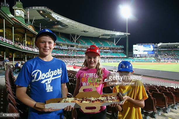 Dodgers fans pose with a two foot hotdog during the match between Team Australia and the LA Dodgers at Sydney Cricket Ground on March 20 2014 in...