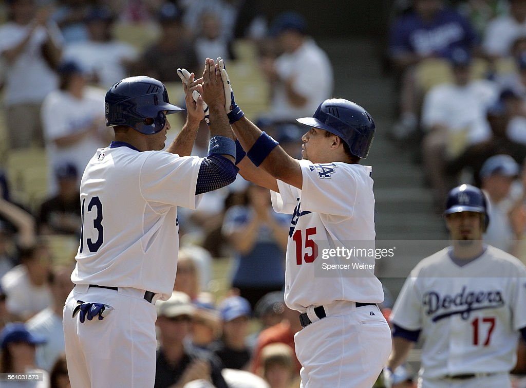 Dodgers Rafael Furcal right gets a high–five at home plate by teammate Oscar Robles after he hitting a two–run homerun off Milwaukee Brewers pitcher...