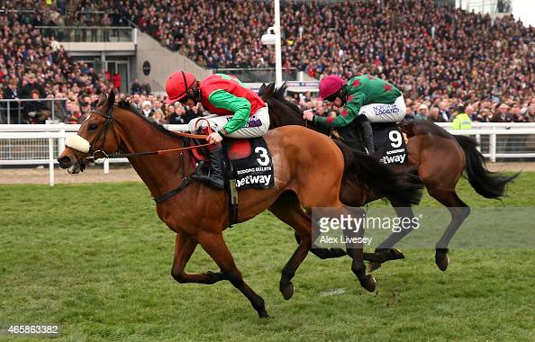 Dodging Bullets ridden by Sam TwistonDavies passes in front of the grandstand ahead of Somersby ridden by Brian Hughes to win the Betway Queen Mother...