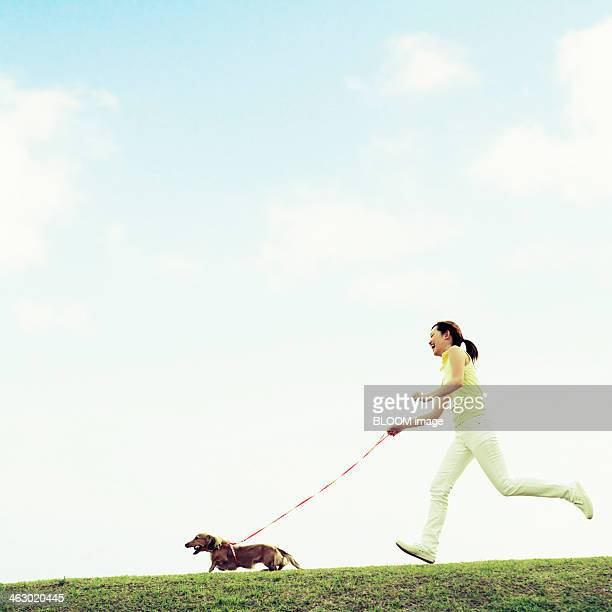 Dog And Woman Running Through The Lawn