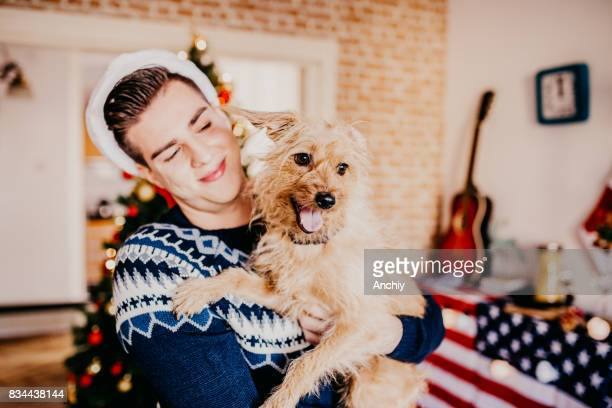 Dog and young man having fun in front of a Christmas tree