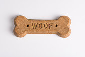 "Dog biscuit with the word ""woof"". Shot on white seamless."