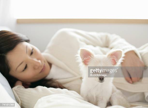 Dog closing eyes by woman on bed