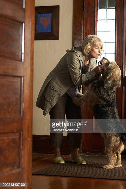 Dog greeting mature woman in entryway of house, side view