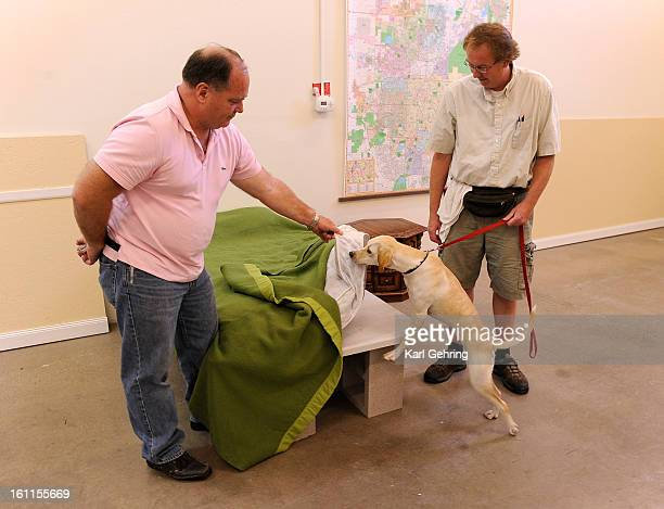 Dog handlers Mark Campbell left and Walter Penny right watched as Macaroni sniffed a mattress for bedbugs during a training session Thursday night...