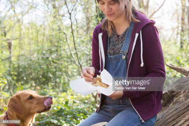 Dog is licking her lips, looking up at woman eating sandwich outdoors.