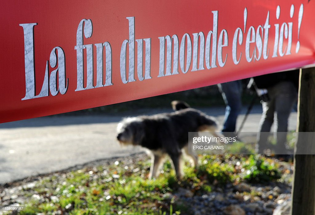 A dog is pictured under an information board for a restaurant reading 'The end of the world, is here' on December 20, 2012 in the southwestern village of Bugarach near the 1,231 meter high peak of Bugarach, one of the few places on Earth some believe will be spared when the world ends on December 21, the end of an era that lasted over 5,000 years, according to the Mayan 'Long Count' calendar. French authorities have pleaded with New Age fanatics, sightseers and media crews not to converge on the tiny village. AFP PHOTO / ERIC CABANIS