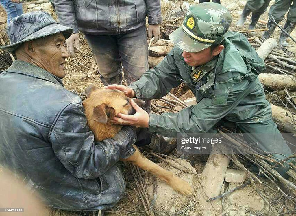 A dog is rescued by soldiers from a collapsed house 77 hours after the earthquake on July 25, 2013 in Minxian, China. At least 95 people were killed and more than 1,000 people injured after a 6.6-magnitude earthquake jolted the border of Minxian county and Zhangxian county in Gansu province on Monday morning.