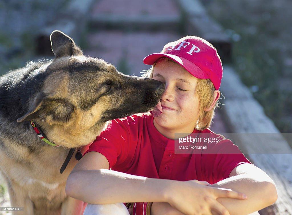 Dog licking Caucasian boy's face : Stock Photo