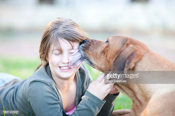 Dog licking girl's face