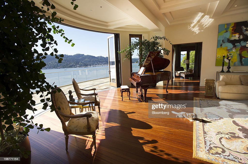 A dog lies on the floor near a piano in the living room of a 15,000 square-foot custom built home on Belvedere Island in Marin County, California, U.S., on Wednesday, Dec. 19, 2012. The builder couldn't find a buyer for the brand-new waterfront mansion he listed in January for $45 million. He hopes one will turn up at a Dec. 30 auction, where the starting bid will be $25 million. Photographer: David Paul Morris/Bloomberg via Getty Images