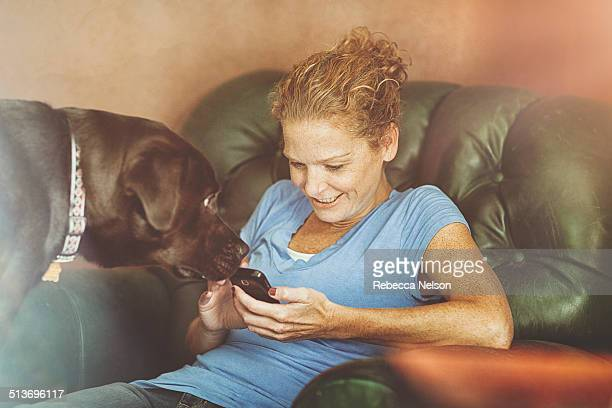 dog looks on as woman checks her smart phone