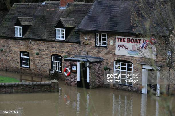 A dog looks out of the window of The Boat Inn public house which flooded at Jackfield near Telford in Shropshire as the river Severn burst its banks