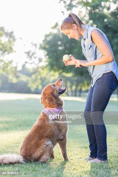 Dog owner prepares to toss ball for dog to fetch