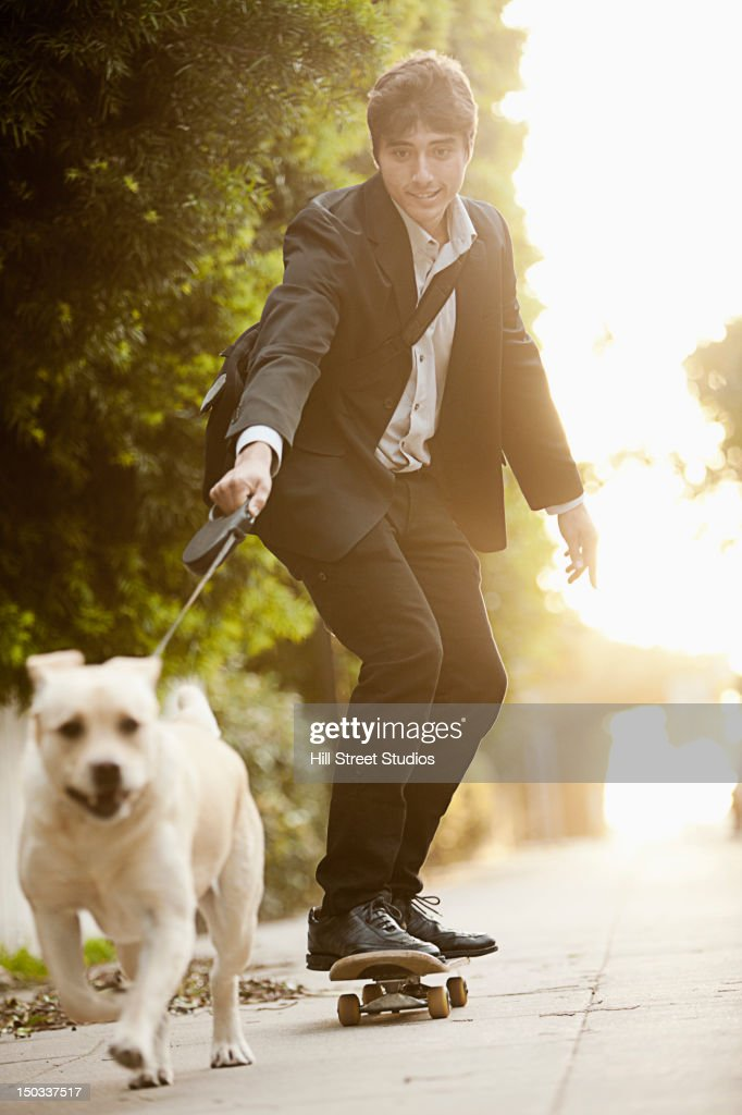 Dog pulling Caucasian businessman on skateboard