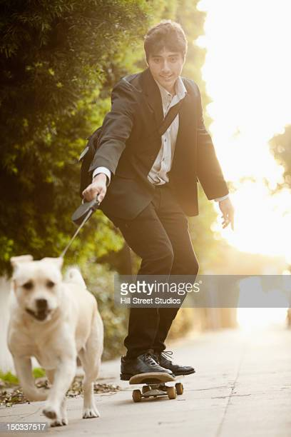 Dog pulling Caucasian businessman on skateboard