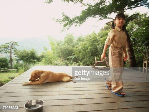 Dog resting, girl walking away : Stock Photo