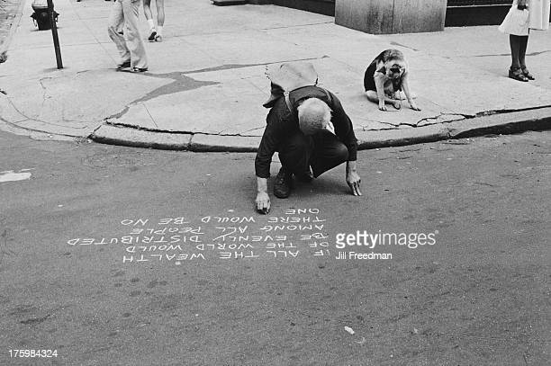 A dog sits on the pavement while a man writes a slogan about economic reform in chalk on the road University Place Greenwich Village New York 1978