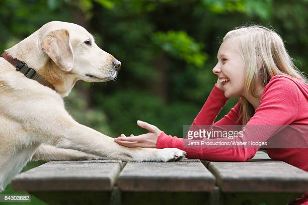 Dog sitting across from girl on picnic table