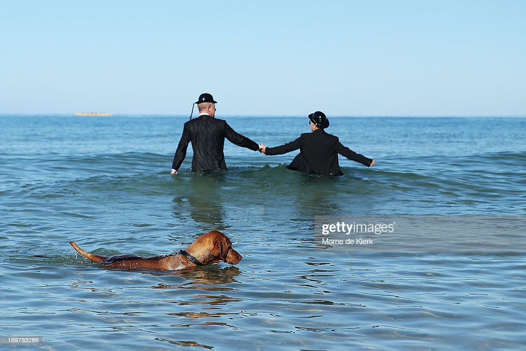 A dog swims by as participants stand in the water while wearing suits and bowler hats as part of an art installation created by surrealist artist Andrew Baines on January 20, 2013 in Adelaide, Australia.
